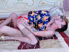 Crossdressed platinum blonde in a flowery robe and red thong in gay twosome